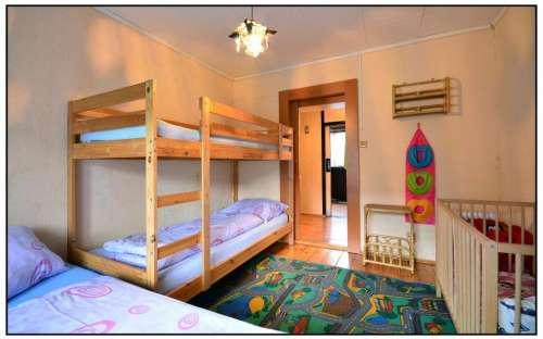 Sypialnia A z łóżeczkiem, dywanem i koszem pełnym zabawek