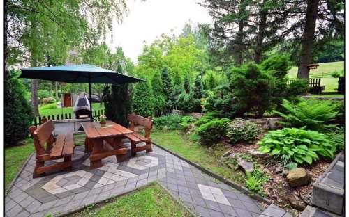 Ogród z kominkiem i parasolem w romantycznym ogrodzie