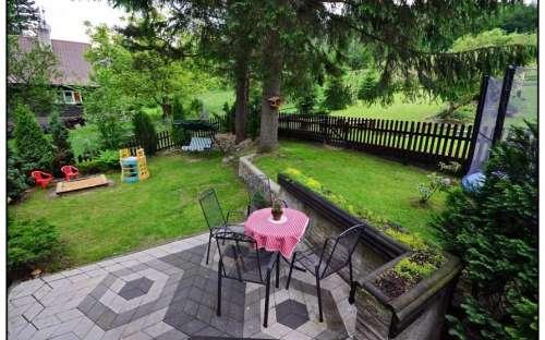 Widok z wejścia do domku - górny taras z miejscem do siedzenia i wykorzystania dla dzieci