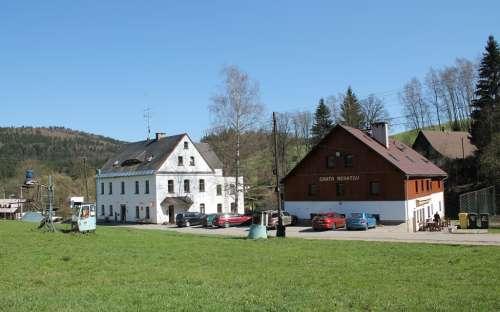 Napravo chata s venkovním posezením a sportovním hřištěm, v budově nalevo se nachází jídelna