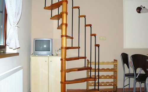 kout s TV a úložným prostorem a schodiště do patra